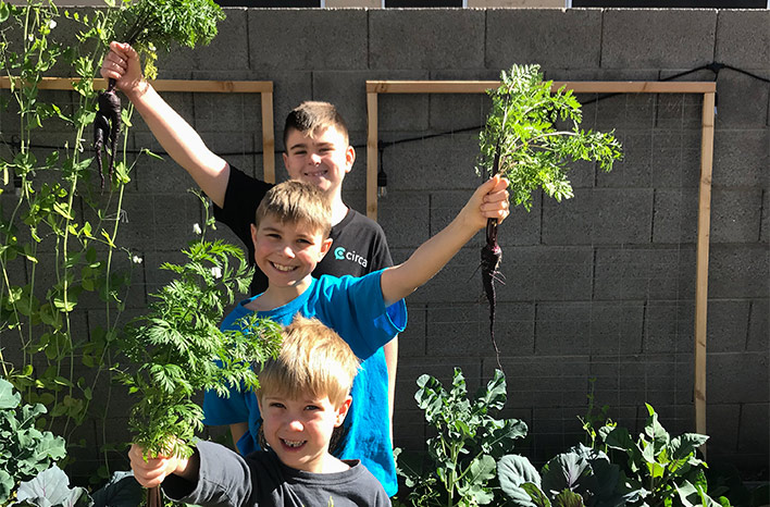Young boys holding veggies grown in the 2020 gardening season.
