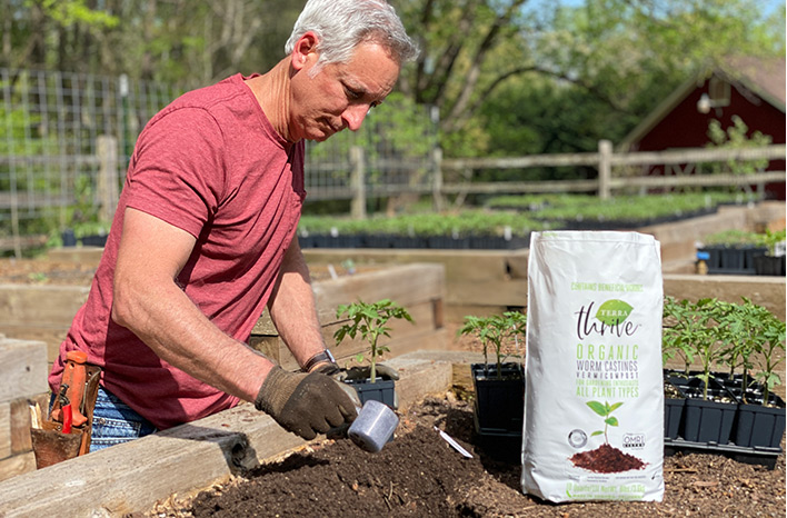 Joe Lamp'l adding compost to a raised garden bed