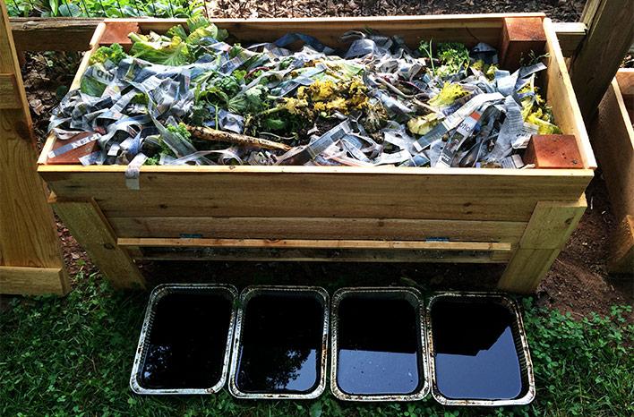 An open worm bin showing trays full of liquid worm waste.